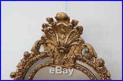 Ancien Miroir mural ovale italien en bois doré sculpté du XIXe siècle