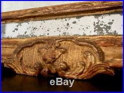 Glace ou miroir doré ancien à fronton ajouré, en bois sculpté et laqué XVIIIe